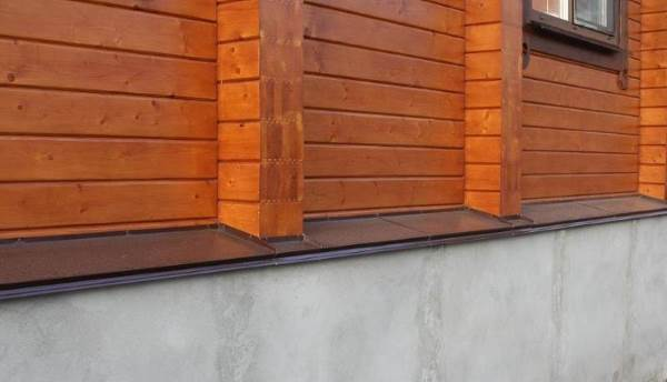 Фото отлива на цоколе дома из бруса